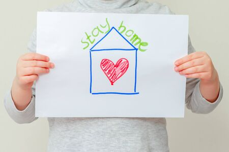 Child's hands holding a picture of house with red heart and words Stay Home. Coronavirus concept.
