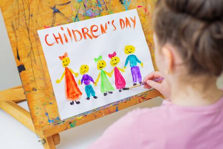 Child is drawing the different children with words Children's Day on a wooden easel for the holiday Happy Children's Day.