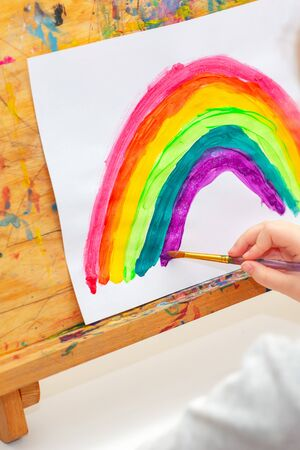 Child is drawing rainbow with watercolors on the sheet of paper on the easel. Creativity concept.