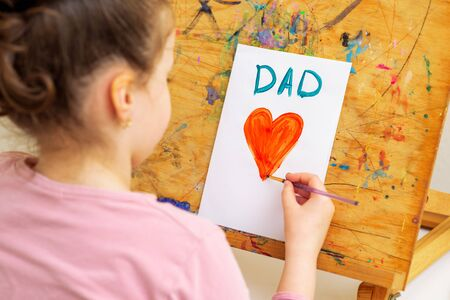 Child is drawing red heart with word Dad greeting card on white paper on an easel. Happy Father's Day concept.