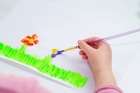 Child is drawing flowers by watercolors on white paper. Children's and Earth day concept. Фото со стока
