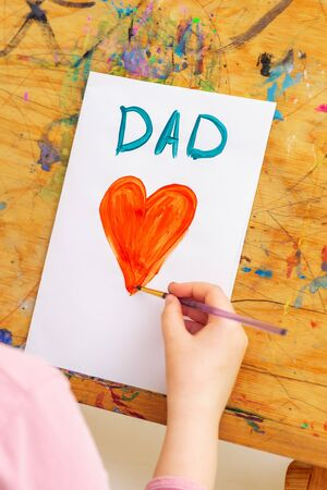 Hand of child drawing red heart with word Dad greeting card on white paper on an easel. Family and Father's Day concept. Banque d'images