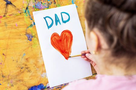 Hand of child drawing red heart with word Dad greeting card by watercolors on white paper on an easel. Father's Day and family concept.