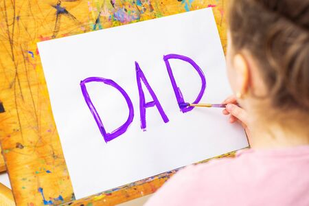Hand of child drawing handwritten purple word Dad greeting card on white paper on easel. Family and Father's Day concept.