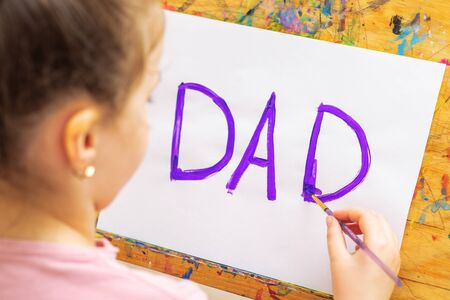 Child is drawing purple word Dad greeting card on white paper on easel. Father's Day concept.