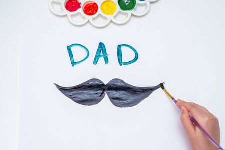 Top view of child's hand drawing black mustache with word Dad on white paper. Happy Father's Day concept. Banque d'images