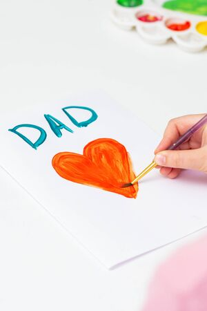 Hand of child drawing red heart with word Dad greeting card on white paper. Family and Father's Day concept. Banque d'images