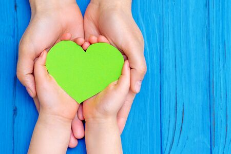 Top view of green heart in hands of man and girl on wooden blue background. Save the world and love nature planet concept.