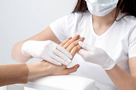 Manicurist is holding fingers of woman with beige manicure in salon.