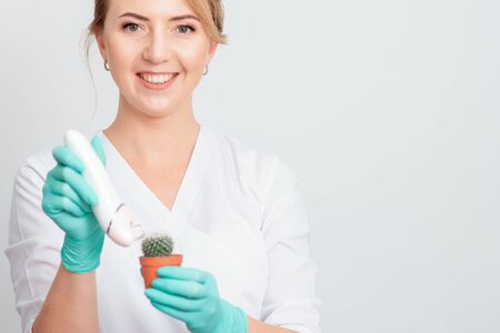 Cosmetologist is shaving green cactus in a brown pot with electric epilator wearing gloves smiling on white background. Concept of depilation, epilation and removal hair.