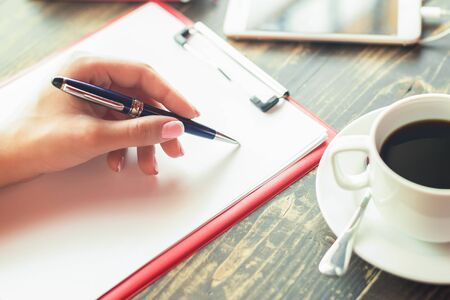 Woman's left hand writing on white sheet of paper with cup of coffee and smartphone on the table in cafe.