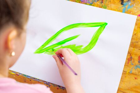 Child's hand drawing green leaf with brush by watercolors on a paper on an easel. Earth day concept. Imagens