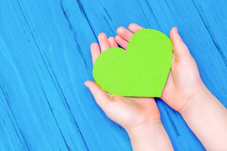 Top view of hands of child holding green heart on wooden blue background. Copy space. Concept of environmental protection and Earth day.
