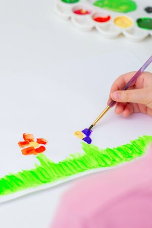 Child's hand drawing flowers on white sheet of paper. Children's and Earth day concept.