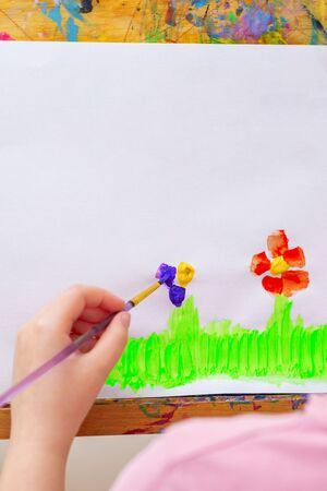 Hand of child drawing flowers on green grass with brush by watercolors on white paper on an easel.