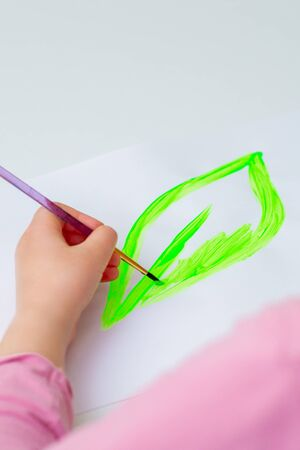 Child's hand drawing green leaf by watercolors on white sheet of paper. Earth day concept.