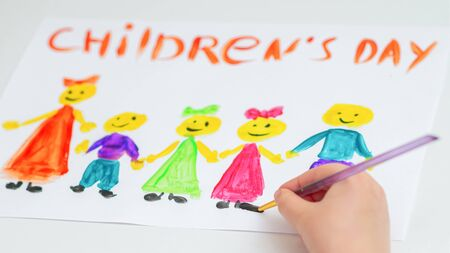 Hand of child drawing the different colorful children with words Children's Day on a white paper. Archivio Fotografico