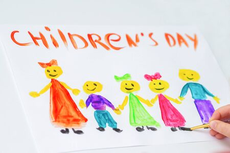 Hand of girl drawing children with text Children's Day on white paper. Happy Children's Day concept.