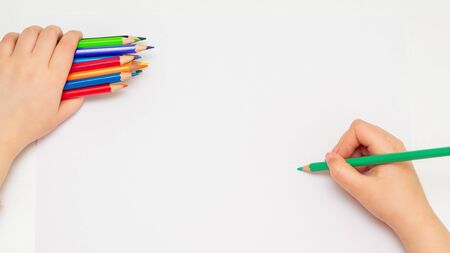 Top view of little hand of child drawing on blank paper by green pencil with bunch of colorful pencils in her hand. Selective focus.