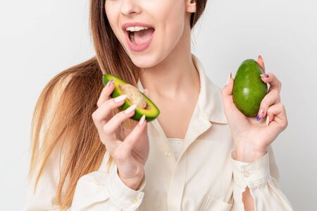 Portrait of pleasantly surprised woman with a two avocado on white background. Stock fotó