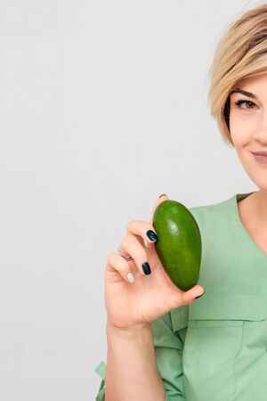 Portrait of caucasian smiling cosmetologist woman with a two avocado on white background.