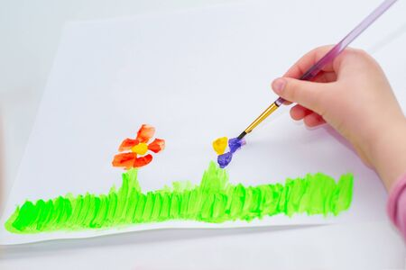 Hand of child drawing flowers by watercolors on white paper. Children's and Earth day concept.