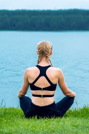 Back view of young woman is doing yoga exercise on grass of the shore of the lake.