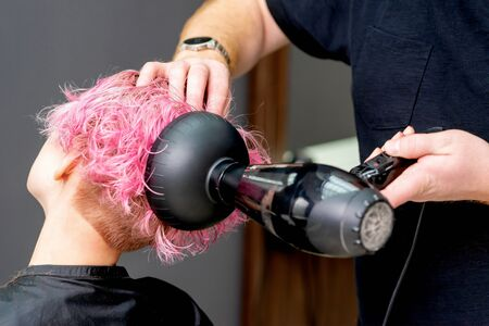 Close-up hairdresser hands are drying pink hair with hair dryer in hair salon.