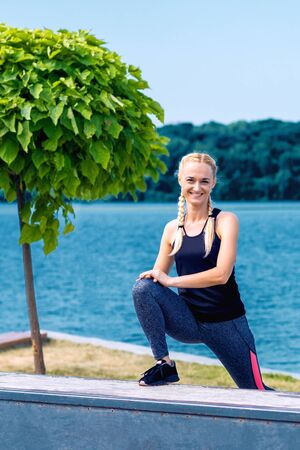 Portrait of woman in sport style clothes by the lake in summer. Banco de Imagens