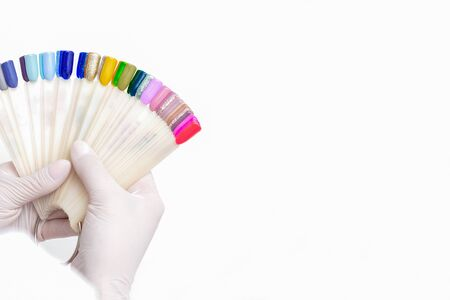 Manicurist hands are holding manicure nail color samples palette on white background.