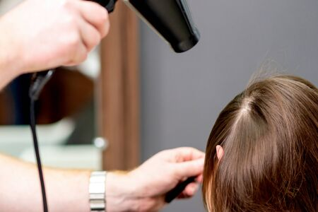 Hairdresser's hands blow drying hair of woman at the beauty salon.