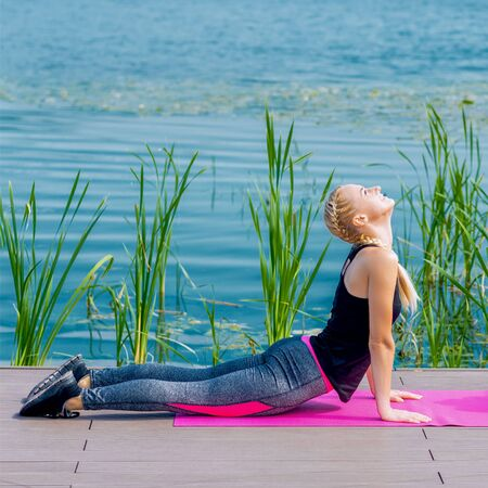 Healthy woman is stretching on the grass at the shore of the lake.