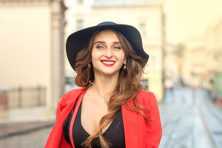 Outdoor portrait of young elegant fashionable woman wearing trendy hat walking in street of European city.