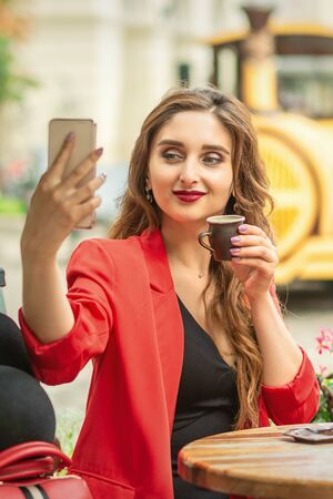 Pretty young girl is taking a selfie on a smartphone while sitting at a table at an outdoor cafe.