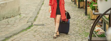 Beautiful young business woman walking on the tram track of a city street with blue travel bag. Imagens