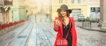 happy young woman walking and carrying hand luggage using mobile phone on the street.