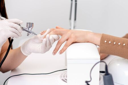 Manicure master is painting finger nails in beige color using airbrush.