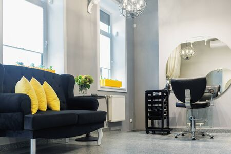 Interior of modern beauty and hairdresser salon with armchair and mirror in yellow and black tones. Banque d'images