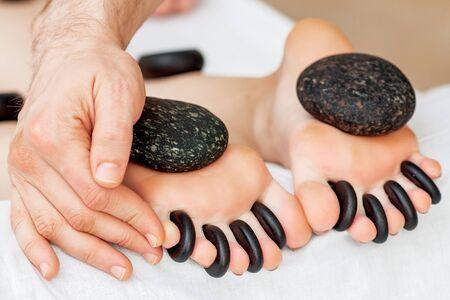 Hands of masseur putting hot little black stones between female toes for feet massage