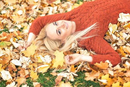Beautiful young caucasian woman lying down on yellow leaves looking at camera in Autumn Park