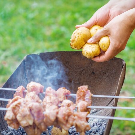 Hands of man prepares barbecue meat with potatoes on skewer by grill on fire outdoors. Concept of lifestyle rustic food preparation