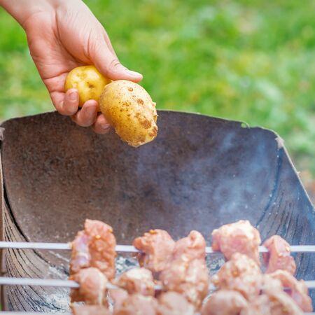 Hands of man prepares barbecue meat with potatoes on skewer by grill on fire outdoors. Concept of lifestyle rustic food preparation Archivio Fotografico