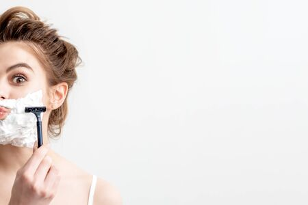 Beautiful young caucasian woman shaving her face by razor on white background. Pretty woman with shaving foam on her face 写真素材