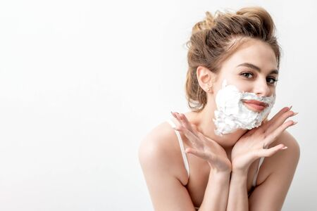Beautiful young caucasian woman with shaving foam on her face posing on white background