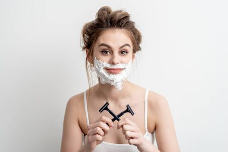 Beautiful young caucasian woman with shaving foam on her face and two razors in her hands on white background Archivio Fotografico