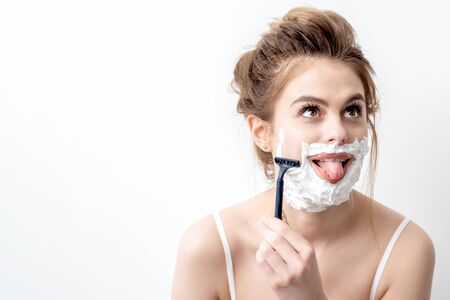 Beautiful young caucasian woman shaving her face by razor on white background. Pretty woman with shaving foam on her face Banco de Imagens