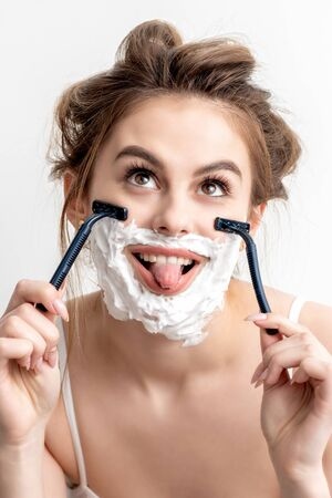 Beautiful young caucasian woman shaving her face by two razors with tongue out on white background. Banco de Imagens