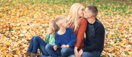 Portrait of young family sitting in autumn leaves. Parents kissing and sitting with children in the autumn park