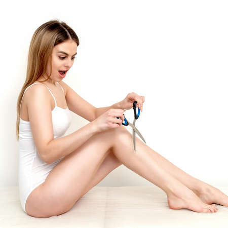 Beautiful young slim caucasian woman cutting hair on her legs by scissors on white background. Depilation concept