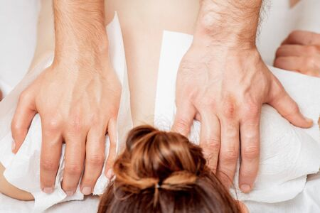 Back massage on back of woman in four hands by two male therapists.